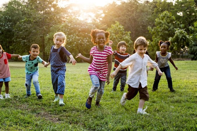 Group of multi-ethnic preschoolers running outside
