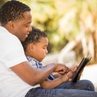 African American father with son reading a book