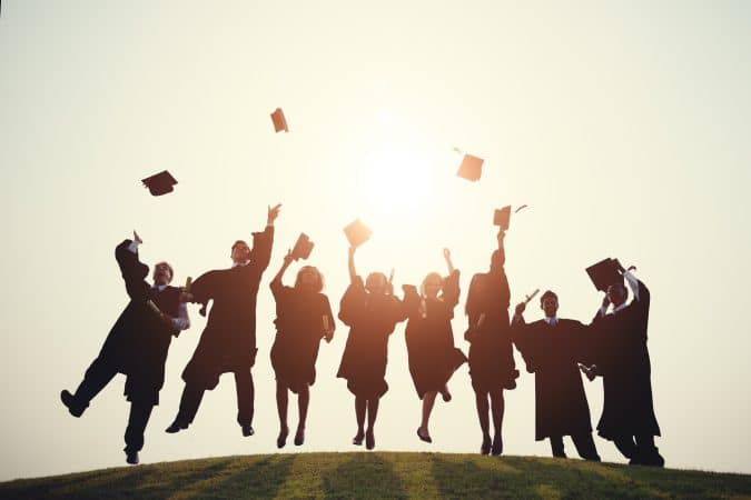 graduates in cap and gown outside