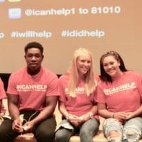High school students with I Can help t-shirts on stage