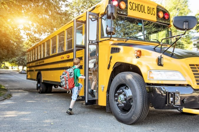 elementary student getting on school bus