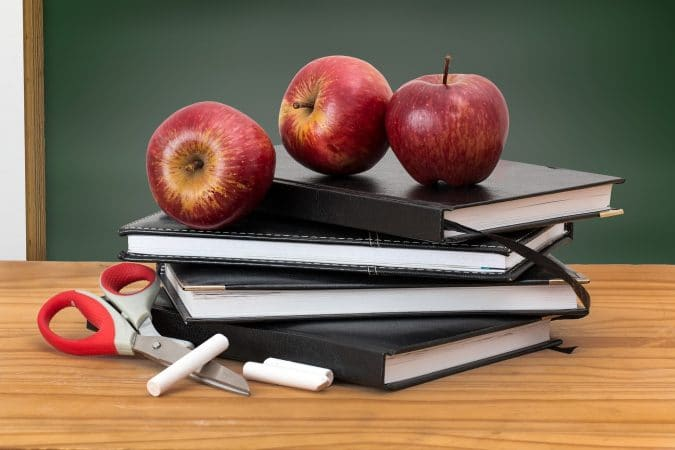 stack of books with apples on top of them