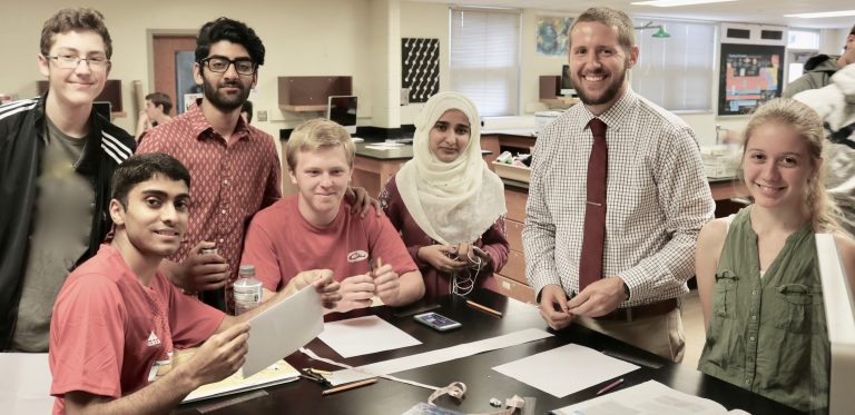six students, one teacher at lab table