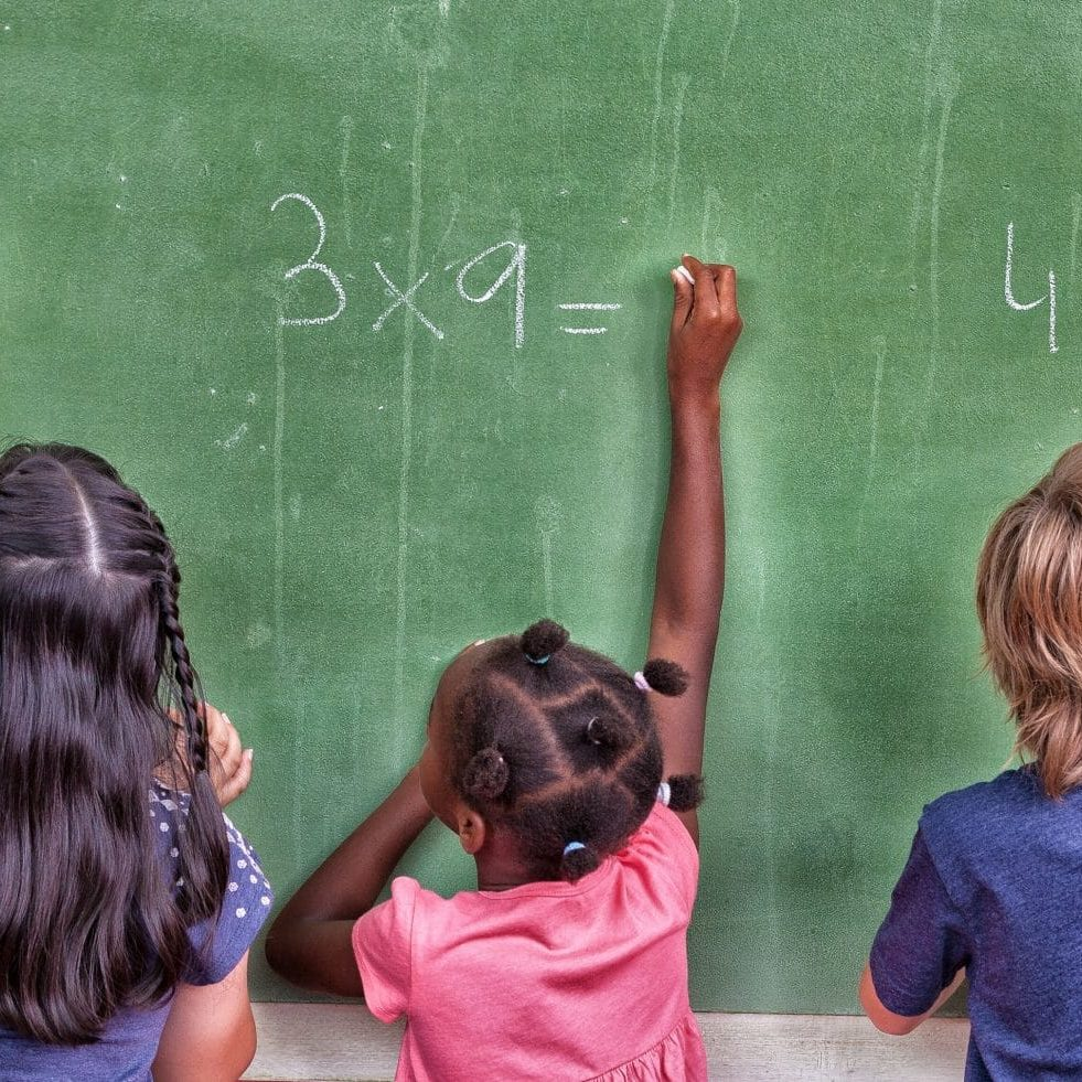 three elementary students doing math problems on chalkboard