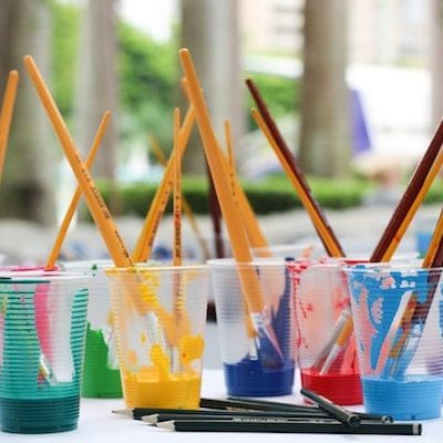paintbrushes in paint cups