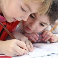 Two young girls writing in notebook